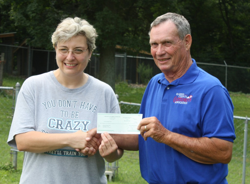Penny Edwards, Animal Refuge Center manager accepts a $1,500 check from the Kentucky Cattlemen's Foundation, given by Chuck Crutcher, Hardin County Cattlemen's Association.